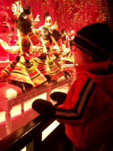 Child looking at Parisian window display at Christmastime